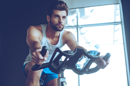 Confident cycler. Low angle view of young man in sportswear cycling at gym 写真素材