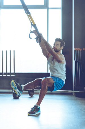 Fell your balance and strength. Full-length of young man in sportswear exercising at gym
