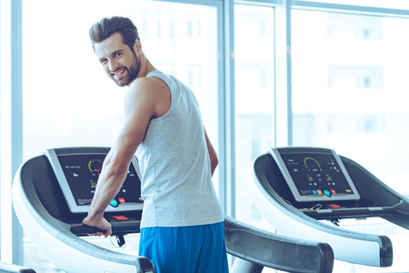only one man: Handsome on treadmill. Rear view of young handsome man in sportswear standing on treadmill in front of window at gym and looking at camera with smile Stock Photo