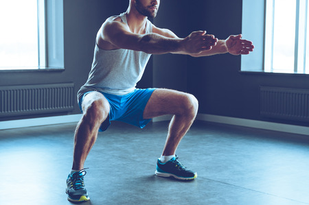 Deep squat. Part of young man in sportswear doing squat at gym Stock Photo