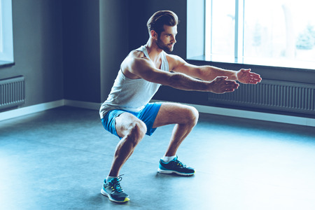 Perfekte Hocke. In voller Länge von jungen Mann in der Sportkleidung im Fitness-Studio hocken Tun