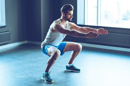 Perfektní dřep. Plná délka mladý pohledný muž ve sportovní dělání squat v tělocvičně