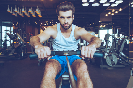 Feel his motivation. Front view of confident young man in sportswear doing rowing at gym and looking at camera