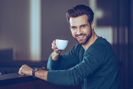 side bar: Salute! Side view of handsome young man holding coffee cup and looking at camera with smile while sitting at bar counter