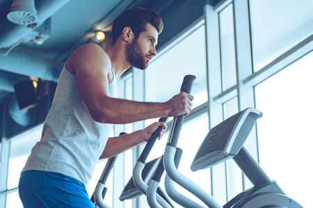 body built: Getting the best body for summer. Low angle side view of young handsome man in sportswear looking away while working out on stepper at gym