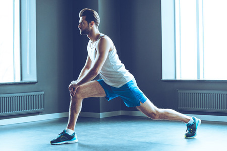 body built: Great stretching. Side view of young handsome man in sportswear doing stretching at gym Stock Photo