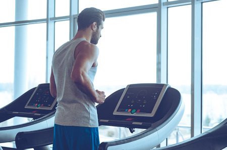 adults: Body power. Young man in sportswear running on treadmill in front of window at gym