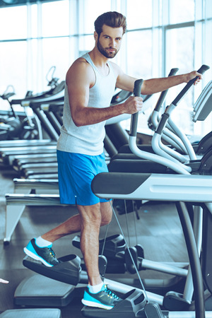 man gym: Concentrated at his workout. Full length side view of young handsome man in sportswear looking at camera while working out on stepper at gym Stock Photo