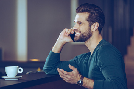 side bar: Great phone call. Side view of handsome young man talking on mobile phone with smile while sitting at bar counter Stock Photo