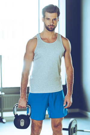 kettle bell: Stronger then yesterday. Young handsome man in sportswear holding kettle bell and looking at camera while standing at gym
