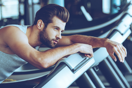 After five miles. Side view of young man in sportswear looking exhausted while leaning on treadmill at gym Stock Photo