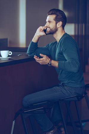 beau mec: Je vous attends! Vue de côté du beau jeune homme parlant au téléphone mobile avec le sourire alors qu'il était assis au comptoir de bar