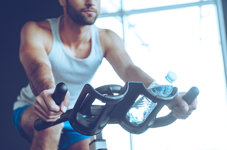 body built: Cycling at gym. Part of low angle view of young man in sportswear cycling at gym Stock Photo