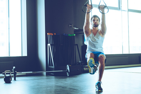 adults: Great TRX workout. Full length of young handsome man in sportswear exercising at gym