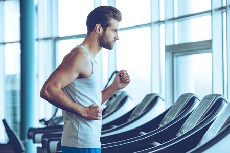Hızlı koşmak. Spor salonunda koşu bandı üzerinde spor çalışan genç adam Yandan görünüm