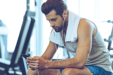 man gym: Preparing for next training circle. Handsome young men in headphones using his smart phone while sitting at gym Stock Photo