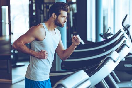 hombres corriendo: Movimiento rápido. Vista lateral del hombre joven en ropa deportiva corriendo en la cinta en el gimnasio