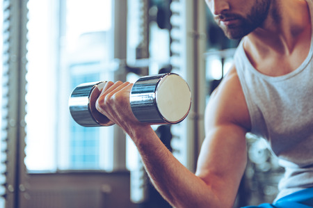 only the biceps: Feel the bicep. Close up part of young man in sportswear exercising with dumbbell at gym