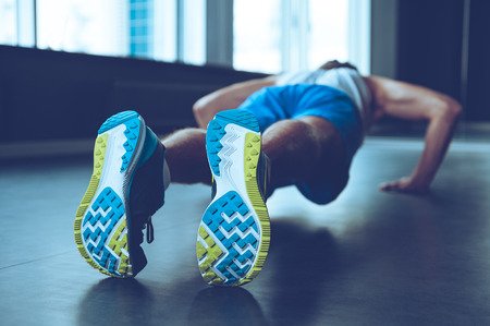 adults only: Perfect push-up. Rear view of young man in sportswear doing push-up at gym Stock Photo