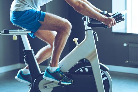 Meilleur entraînement cardio. Vue de côté une partie de jeune homme en tenue de sport cyclisme gym