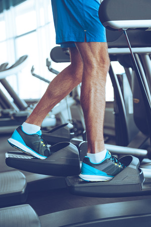 Step by step to get fit. Side view part of young man in sports shoes working out on stepper at gym Stok Fotoğraf - 53665277