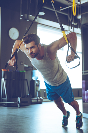 adults only: Strength and power. Full-length of young man in sportswear exercising at gym