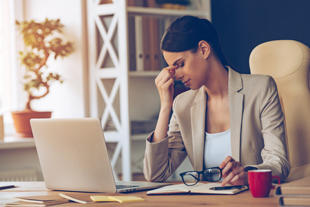 Feeling overworked. Frustrated young beautiful businesswoman looking exhausted while sitting at her working place and carrying her glasses in hand