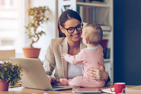 newborn baby mother: Working together is so fun! Cheerful young beautiful businesswoman looking at her baby girl with smile while sitting at her working place Stock Photo