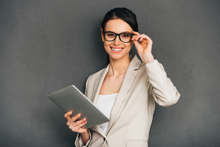 Can I help you? Beautiful young cheerful businesswoman adjusting her glasses and holding digital tablet while standing against grey background