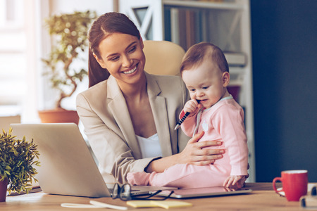 Helping to mommy. Little baby girl chewing pen while sitting on office desk with her mother in office Фото со стока