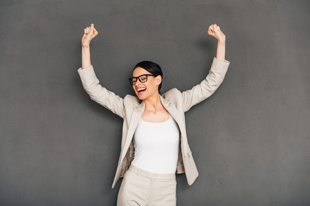 hurray: Hurray! Cheerful young businesswoman in glasses gesturing and keeping her mouth open while standing against grey background