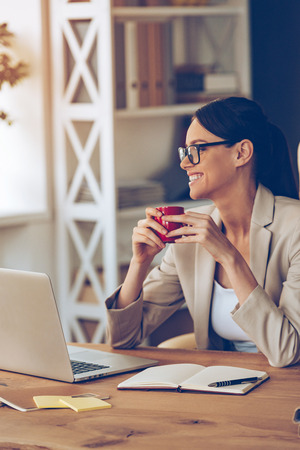 Enjoying her working day. Cheerful young beautiful businesswoman in glasses holding coffee cup and looking away with smile while sitting at her working place
