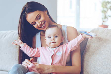 baby sitting: Here I am! Beautiful young woman holding baby girl with toy on her knee sand looking at her with love while sitting on the couch at home
