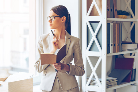 mujer pensativa: Tengo que hacer algunos cambios! Pensativo joven hermosa en vidrios que sostienen el cuaderno y mirando por la ventana mientras está de pie en su lugar de trabajo