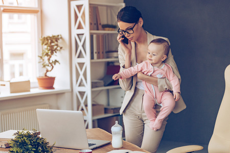 It is not easy to be a working mom! Young beautiful businesswoman talking on mobile phone and looking at laptop while standing with her baby girl at her working place Stock Photo
