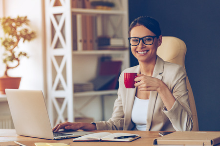 Beautiful expertise. Cheerful young beautiful businesswoman in glasses holding coffee cup and looking at camera with smile while sitting at her working place Stockfoto