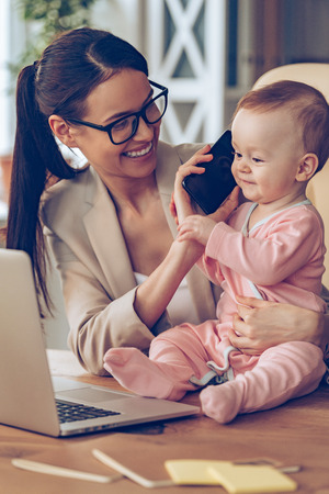 Say hello to dad! Little baby girl talking on mobile phone while sitting on office desk with her mother in office