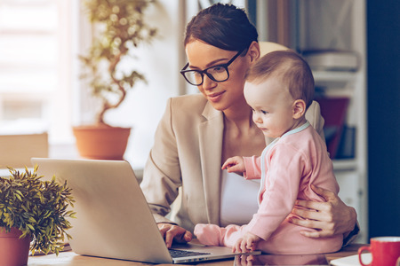 Working together. Young beautiful businesswoman using laptop while sitting with her baby girl at her working place Imagens