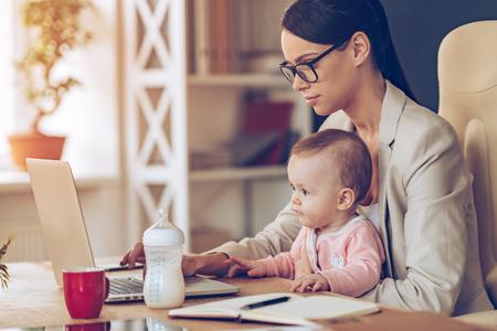 madre trabajando: moderno de negocios que puede manejar todo. Vista lateral de la joven y bella mujer de negocios usando la computadora portátil mientras está sentado con la niña en sus rodillas en su lugar de trabajo Foto de archivo