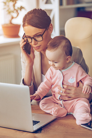 working place: Working with baby. Young beautiful businesswoman talking on mobile phone and looking at laptop while sitting with her baby girl at her working place Stock Photo