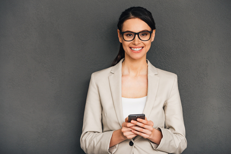 woman  glasses: Great news! Beautiful young cheerful businesswoman holding her smart phone and looking at camera with smile while standing against grey background