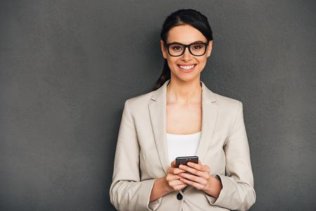 mujer alegre: ¡Una gran noticia! joven y bella mujer de negocios alegre celebración de su teléfono inteligente y mirando a cámara con una sonrisa mientras está de pie contra el fondo gris Foto de archivo