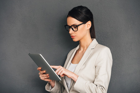easier: Technologies make business easier. Side view of beautiful young businesswoman in glasses using her digital tablet while standing against grey background Stock Photo