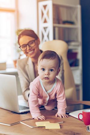 madre trabajadora: madre de trabajo moderno. El peque�o beb� que mira a la c�mara mientras se arrastra en su lugar de trabajo madres