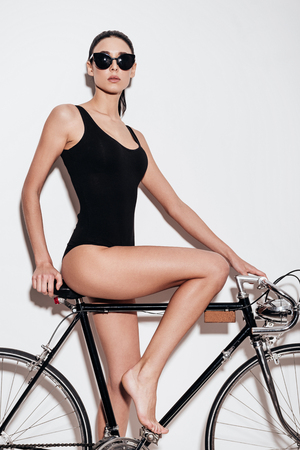 Beautiful young woman in black swimsuit posing and looking at camera while leaning to bicycle against white background