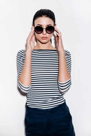 fashionable woman: Beautiful young woman adjusting her sunglasses and looking at camera while standing against white background Stock Photo