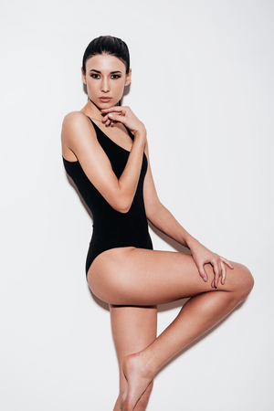 expresion corporal: Joven y bella mujer posando en traje de baño negro y mirando a la cámara mientras está de pie contra el fondo blanco