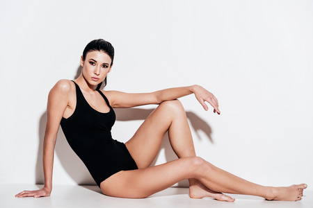 Side view full length of beautiful young woman in black swimsuit posing and looking at camera while sitting against white background