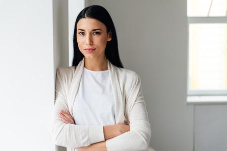 Schöne junge Frau hält die Arme verschränkt und Blick in die Kamera, während in der Nähe von weißen Wand