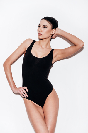 Beautiful young woman in black swimsuit holding hand on hip and looking away while standing against white background